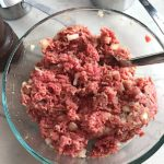 Raw Meatloaf mixed in bowl with spoon. This 5-Ingredient Easy Meatloaf recipe may be short on ingredients, but it is loaded with flavor. The lack of breadcrumbs means you don't have them soaking up the juices, so the meat stays moist - and it's gluten free too! Parmesan cheese, onion, egg, ketchup, salt, and pepper are all that go into this yummy loaf of goodness!