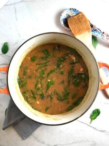 Creamy Tomato Soup in a soup pot on napkin on counter with wood spoon on side. It has Ground Chicken and Spinach is creamy and chunky and has a ton of deep flavor. AND it is healthy! It uses all white meat ground chicken that you cook until it is incredibly browned for some serious flavor. Then tomato paste adds the flavor back drop for the soup and a flour roux plus broth creates the amazing creaminess! Finally Spinach is your veggie boost.