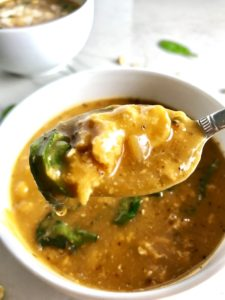 Creamy Tomato Soup on a spoon over bowl. This soup with Ground Chicken and Spinach is creamy and chunky and has a ton of deep flavor. AND it is healthy! It uses all white meat ground chicken that you cook until it is incredibly browned for some serious flavor. Then tomato paste adds the flavor back drop for the soup and a flour roux plus broth creates the amazing creaminess! Finally Spinach is your veggie boost.