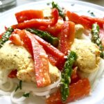 Close up of Mustard Chicken with Red Peppers and Asparagus over rice noodles.