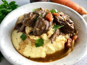 Cooked short ribs on top of creamy polenta in a bowl with sauce, carrots, and onions. Bowl sitting on counter.