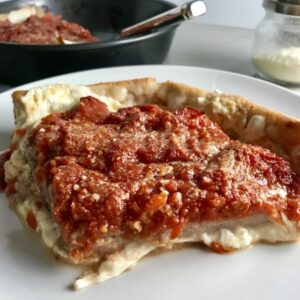slice of deep dish pizza on a plate with pan and parmesan in background