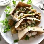 Pitas on plate stuffed with meatballs and hummus with yogurt sauce on top and parsley