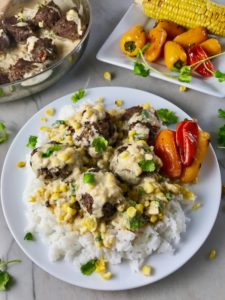 Chipotle Meatballs with corn sauce over rice on white place with peppers on side. Plate on marble counter with peppers on plate in back and pan with meatballs in back.