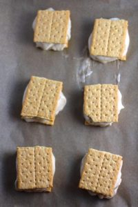6 Graham Cracker and Banana Ice Cream Sandwiches on parchment paper. Banana Ice Cream is literally just 2 ingredients, Frozen Bananas and Almond Milk.  Add in crunchy Graham Crackers as the 3rd ingredient and you have a delicious healthy Banana Ice Cream Sandwich!  If you have never tried banana ice cream, you are in for a treat!  It tastes just like soft serve ice cream.
