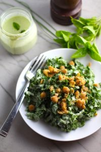 Basil & Chive Yogurt Dressing on Kale Salad with chickpeas on top on white plate on counter with basil leaves and dressing jar in back. This dressing with Lemon and Honey is creamy, light, savory, and a little bit sweet. It takes only minutes to make this delicious homemade dressing.  Basil & Chive Yogurt Dressing is perfect for salads, for drizzling over roasted veggies, steak, chicken, or fish, and amazing for dipping fries into!!