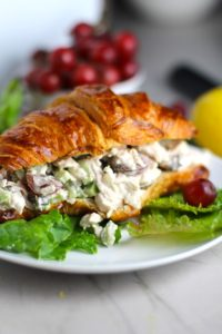 Lemon Basil Chicken Salad with Grapes on a croissant on plate with lettuce and grapes in background. This recipe is simple, but the taste is anything but simple. It has layers of flavors and textures. You get the hearty texture of the chicken, brightness from the lemon, the fresh and fragrant basil, a slight bite from the onion, and a huge juicy burst of sweetness from the grapes.