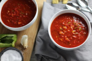 This Roast Red Pepper Gazpacho recipe is Summer in a bowl. It's cool, tangy, crunchy, fresh, and creamy. The base is tomato, but this Gazpacho recipe puts Roast Red Pepper in the starring role, which brings another layer of creamy sweetness. Then you get the crunch from the green pepper, cucumber, garlic and scallions.