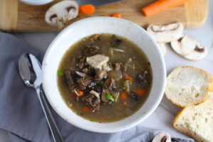 Chicken and Mushroom Soup in white bowl with raw mushrooms, carrots, wood cutting board, bread, and spoon on counter. This Slow Cooker Chicken and Mushroom Soup is warm, hearty, comforting, earthy, and just devine. The mix of blended and chunky mushrooms with carrots, onions, celery, shredded chicken, and herbs gives you a perfect bite every time.
