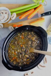 Chicken and Mushroom Soup in a Slow Cooker Pot with wood spoon on counter with cutting board next to it and raw mushrooms and carrots around. This Slow Cooker Chicken and Mushroom Soup is warm, hearty, comforting, earthy, and just devine. The mix of blended and chunky mushrooms with carrots, onions, celery, shredded chicken, and herbs gives you a perfect bite every time.