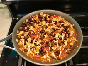 Meat, tomatoes, green chilis, and black beans in skillet. This Taco Casserole has corn tortillas layered with browned ground chicken seasoned with smokey mexican spices, black beans, tomatoes, and cheese, and then more cheese.