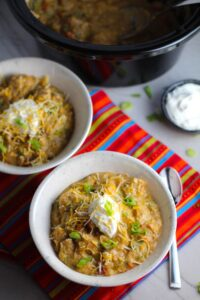 2 Bowls of Chipotle Chicken Enchilada Stew with sour cream and scallion slices as garnish and slow cooker pot in background. It's one of my Prepped Freezer Meal recipes and it's creamy, cozy, hearty, cheesy, and slightly spicy. All ingredients freeze raw, thaw, then cook in the slow cooker or in the oven. It's a stew because it's thick and hearty with bites of chicken, carrots, onion, chipotle peppers, cumin, garlic and tortilla chips that melt down to thicken this delicious stew.