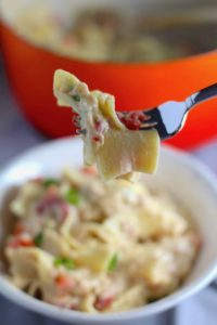Easy Tuna Casserole bite on a fork over a bowl with pot in background. This is a creamy and delicious comfort dish with tuna and noodles and a surprise pop of sweet from Pimiento.  This easy recipe is completely from scratch (no canned soup here!) but I can promise you it's so easy and only takes 30 minutes because it's a Casserole that you can make entirely on the stove top!