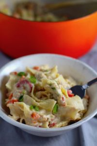 Easy Tuna Casserole in a bowl with a fork with pot in background. This is a creamy and delicious comfort dish with tuna and noodles and a surprise pop of sweet from Pimiento.  This easy recipe is completely from scratch (no canned soup here!) but I can promise you it's so easy and only takes 30 minutes because it's a Casserole that you can make entirely on the stove top!