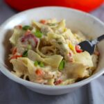 Stove top Easy Tuna Casserole in a bowl with a fork and pot in background. This is a creamy and delicious comfort dish with tuna and noodles and a surprise pop of sweet from Pimiento.  This easy recipe is completely from scratch (no canned soup here!) but I can promise you it's so easy and only takes 30 minutes because it's a Casserole that you can make entirely on the stove top!