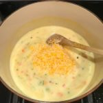 Spoon mixing shredded cheese into sauce in pot for Easy Tuna Casserole. This is a creamy and delicious comfort dish with tuna and noodles and a surprise pop of sweet from Pimiento.  This easy recipe is completely from scratch (no canned soup here!) but I can promise you it's so easy and only takes 30 minutes because it's a Casserole that you can make entirely on the stove top!