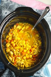 Moroccan Chicken Chili with Chickpeas in a Slow Cooker Pot with spoon n blue towel. Its loaded with comforting and healthy ingredients and spices. You get warmth from Ginger, Turmeric, Garlic, and Coriander. Then tons of hearty flavor from browned ground chicken and Shallots. And creaminess from the Carrots and Chickpeas. You can make it ahead and freeze it until you are ready to cook it!