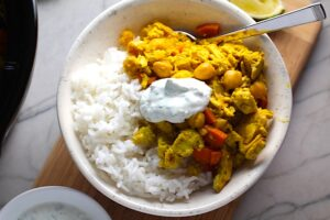 Moroccan Chicken Chili in bowl over white rice with a dollop of Cilantro Lime Yogurt on top. Moroccan Chicken Chili with Chickpeas is loaded with comforting and healthy ingredients and spices. You get warmth from Ginger, Turmeric, Garlic, and Coriander. Then tons of hearty flavor from browned ground chicken and Shallots. And creaminess from the Carrots and Chickpeas. You can make it ahead and freeze it until you are ready to cook it!
