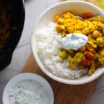 Moroccan Chicken Chili in bowl over white rice with a dollop of Cilantro Lime Yogurt on top and in a bowl to the left. The slow cooker is in background with chili. Moroccan Chicken Chili with Chickpeas is loaded with comforting and healthy ingredients and spices. You get warmth from Ginger, Turmeric, Garlic, and Coriander. Then tons of hearty flavor from browned ground chicken and Shallots. And creaminess from the Carrots and Chickpeas. You can make it ahead and freeze it until you are ready to cook it!