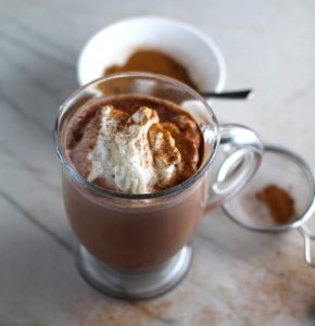 Pumpkin Spice sprinkled on top of whipped cream on hot cocoa. Spice blend in a sifter to the right and in a bowl in background. Recipe has 4 simple ingredients and takes minutes to make! PLUS, here are 20 EASY WAYS TO USE this Spice blend, many with no baking at all!