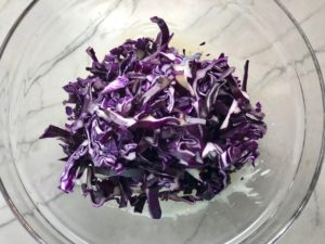 Cabbage shredded in bowl for Asian Lettuce Wraps. They are a fantastic way to use leftover Turkey or Chicken transforming it with new delicious flavors and textures. The turkey is stir fried with carrots, red pepper, and brussel sprouts in a flavorful ginger, garlic, & sesame sauce. It's layered in lettuce wraps with rice and a cool, crunchy purple cabbage sesame slaw. Serve with a Garlic Honey Soy Sauce....YUM!!!