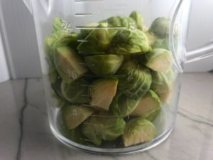 Cut raw Brussel Sprouts in measuring cup for the Easy Bacon Brussel Sprouts and Chicken recipe. It's a perfect quick Fall Recipe! It has a creamy sauce filled with salty bacon, earthy and almost nutty seared brussel sprouts, and hearty healthy chicken. Serve over rice (or Quinoa or pasta!).