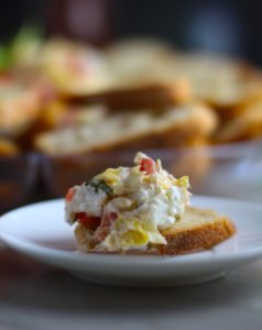 Close up of Bruschetta topping on crostini with platter in background.It combines fresh tomatoes, artichoke hearts, garlic, basil, olive oil, and GOAT CHEESE! Top on toasty garlic crostini and you get fresh bright flavors with both crunch and creamy in every bite.