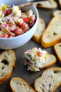 Bruschetta Topping in bowl on pan surrounded by crostini with one crostini topped. It combines fresh tomatoes, artichoke hearts, garlic, basil, olive oil, and GOAT CHEESE! Top on toasty garlic crostini and you get fresh bright flavors with both crunch and creamy in every bite.