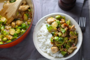 Easy Bacon Brussel Sprouts and Chicken served over white rice in a bowl with orange pot in background. It is a perfect quick Fall Recipe! It has a creamy sauce filled with salty bacon, earthy and almost nutty seared brussel sprouts, and hearty healthy chicken. Serve over rice (or Quinoa or pasta!).