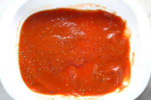 Tomato sauce at bottom of casserole dish for Turkey Ricotta Stuffed Shells in Tomato Sauce. These are the perfect way to repurpose and transform leftover Turkey or Chicken. The Shredded Turkey, Italian seasonings, mozzarella, and ricotta are stuffed in shells and topped with a simple tomato sauce and more melty mozzarella and nutty parmesan, it's a perfect dish that the family will love!