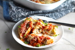 Turkey Ricotta Stuffed Shells in Tomato Sauce on plate cut with casserole dish in background. These are the perfect way to repurpose and transform leftover Turkey or Chicken. The Shredded Turkey, Italian seasonings, mozzarella, and ricotta are stuffed in shells and topped with a simple tomato sauce and more melty mozzarella and nutty parmesan, it's a perfect dish that the family will love!