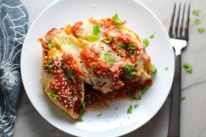 Turkey Ricotta Stuffed Shells in Tomato Sauce on plate with casserole dish in background. These are the perfect way to repurpose and transform leftover Turkey or Chicken. The Shredded Turkey, Italian seasonings, mozzarella, and ricotta are stuffed in shells and topped with a simple tomato sauce and more melty mozzarella and nutty parmesan, it's a perfect dish that the family will love!