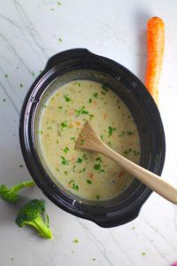Slow Cooker Creamy Broccoli Soup in a crockpot with wood spoon and raw broccoli and carrots on counter.  This is easy, comforting, and delicious! With Carrots, Broccoli, Onion, Garlic, and Oregano, this is one flavorful soup. And, there is no heavy cream, just milk and a little half and half mixed with cornstarch, so it's healthy and gluten free!