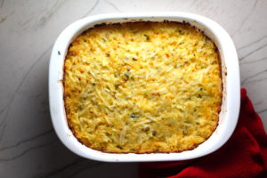 Cheesy Hash Brown Casserole Recipe cooked in casserole dish on counter. This recipe does not disappoint! It's warm, creamy, and full of flavor! And it's the perfect side dish for your holiday dinner.