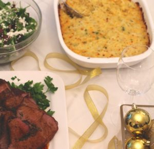 Cheesy Hash Brown Casserole on holiday table with salad, beef roast, and gold ornaments. This recipe does not disappoint! It's warm, creamy, and full of flavor! And it's the perfect side dish for your holiday dinner.