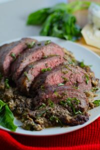 Stuffed Flank Steak cooked and cut on white plate with stuffing oozing out and basil on side. In the stuffing you get mushrooms, onions, and garlic sauteed together. Then they are mixed with fresh parsley and basil, then parmesan, and goat cheese! Roll it all up in Flank Steak and roast for an amazing dinner.