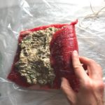 Raw flank steak with Mushroom stuffing spread on top and hand starting to roll the steak from the right side. This Stuffed Flank Steak recipe is oozing with flavor! First, you get mushrooms, onions, and garlic sauteed together. Then they are mixed with fresh parsley and basil, then parmesan, and goat cheese! Roll it all up in Flank Steak and roast for an amazing dinner.