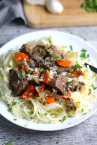 Slow Cooker Beef Stew over Noodles on a plate. This is downhome comfort food that's full of flavor and texture with carrots, onion, garlic, thyme, beef, and more. Now, try pouring that salty, chunky, saucy goodness over noodles...yup, even more amazing! #beefstew #crockpot #slowcooker #easydinners #dinnerrecipes