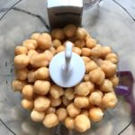 Whole Chickpeas in food processor for Magical Sriracha Hummus. This recipe is seriously the easiest hummus you will ever make and it's perfect for snacking or adding to a meal.  The chickpeas have so much flavor and the Sriracha gives it a kick that is totally addictive!