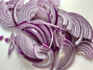 Red Onions sliced before pickling for Slow Cooker Pork Tacos with with Pickled Onions, Shredded Cheese, and Cilantro Lime Crema drizzled on top!  It's such an easy dinner since the pork cooks in the slow cooker to be perfectly seasoned and fall apart tender. #tacos #easydinner #glutenfree #dinner #mexican #pork