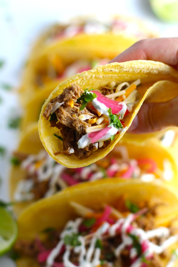Hand holding a Slow Cooker Pork Taco with with Pickled Onions, Shredded Cheese, and Cilantro Lime Crema drizzled on top! It's such an easy dinner since the pork cooks in the slow cooker to be perfectly seasoned and fall apart tender. #tacos #easydinner #glutenfree #dinner #mexican #pork