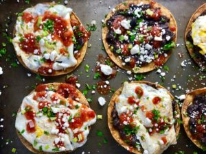 Huevos Tostadas are utterly delicious! They are similar to Huevos Rancheros but are a pick up and eat with your hands version! They have crispy corn tortillas topped with creamy mashed black beans, a salty fried egg, smoky tomato sauce, cheese, and scallions! #huevosrancheros #eggs #brunch #mexicanrecipes #vegetarian #meatlessrecipes #glutenfree