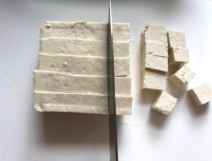 Knife slicing Extra Firm Tofu into pieces for Roasted Tofu Croutons. These are seasoned and toasted for the perfect addition to any salad, pasta, rice, or soup! They get a roasted, almost nutty flavor with a salty and smoky seasoned crust with a chewy bite. Super easy to make, low carb and great source of protein! #croutons #salad #tofu #tofurecipes #vegetarian #plantbased #paleo