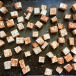 Seasoned tofu pieces on pan for Roasted Tofu Croutons. These are seasoned and toasted for the perfect addition to any salad, pasta, rice, or soup! They get a roasted, almost nutty flavor with a salty and smoky seasoned crust with a chewy bite. Super easy to make, low carb and great source of protein! #croutons #salad #tofu #tofurecipes #vegetarian #plantbased #paleo