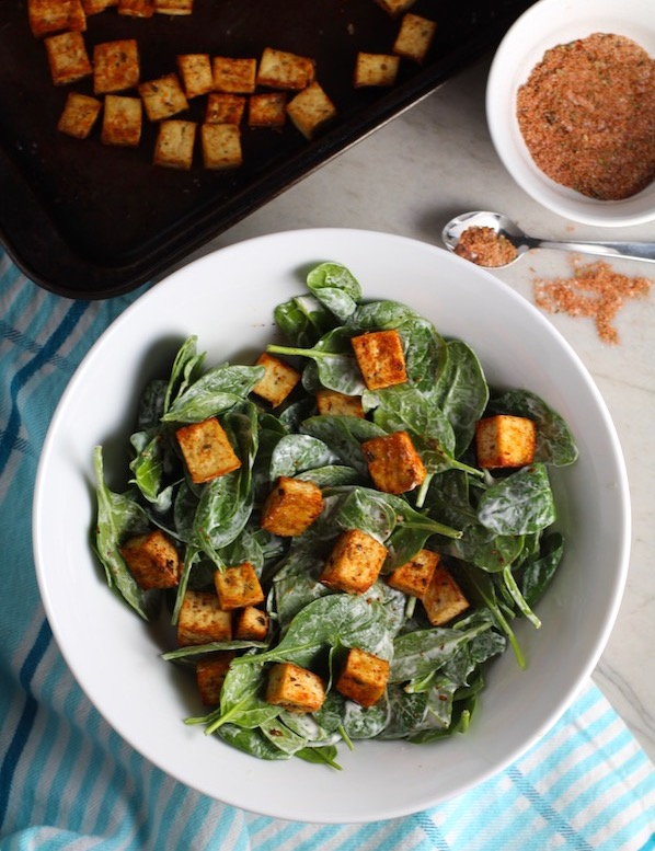 Roasted Tofu Croutons on spinach salad in bowl with croutons on pan in background.  These are seasoned and toasted for the perfect addition to any salad, pasta, rice, or soup!   They get a roasted, almost nutty flavor with a salty and smoky seasoned crust with a chewy bite.  Super easy to make, low carb and great source of protein!  #croutons #salad #tofu #tofurecipes #vegetarian #plantbased #paleo