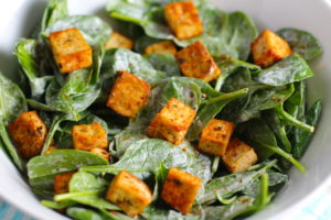 Roasted Tofu Croutons on spinach salad in bowl. These are seasoned and toasted for the perfect addition to any salad, pasta, rice, or soup! They get a roasted, almost nutty flavor with a salty and smoky seasoned crust with a chewy bite. Super easy to make, low carb and great source of protein! #croutons #salad #tofu #tofurecipes #vegetarian #plantbased #paleo