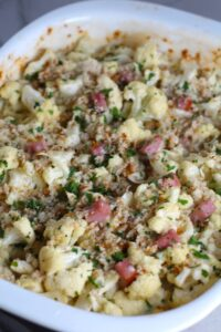 Close up of Cauliflower Cordon Bleu Bake with parsley and breadcrumb topping. It layers in nutty and salty Gruyere Cheese, with a creamy Vegetable broth based sauce with garlic and parsley.  Then the ham and cauliflower are folded into all of this goodness and it's baked in the oven until it all becomes one knock-your-socks-off dish! #cauliflower #lowcarb #glutenfree #casserole #onepot #familydinner #mealprep #easydinner #dinner #healthydinner #healthyfood #healthyrecipes