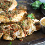 Chicken Chimichurri Rojo on a pan. It is broiled or grilled Chicken topped with a cool, fresh, tangy, and incredibly full-flavored!  The Rojo comes from the addition of red pepper.  All of the ingredients simply get blended in a food processor so it could not be easier!  #chicken #chickenrecipes #chimichurri #easychicken #easydinners #dinner