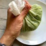 Hand holding cucumber wrapped in paper towel for Garlic and Lime Shrimp with Tzatziki Sauce. The Shrimp is simply sauteed with minced garlic, olive oil, and lemon for big bold flavors. The Tzatziki Sauce is bright and cool with creamy yogurt with fresh cucumber, lime, garlic, and scallion. #shrimp #easydinner #dinner #seafoodrecipes #shrimprecipes