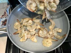 Adding raw shrimp to skillet for Garlic and Lime Shrimp with Tzatziki Sauce.  The Shrimp is simply sauteed with minced garlic, olive oil, and lemon for big bold flavors. The Tzatziki Sauce is bright and cool with creamy yogurt with fresh cucumber, lime, garlic, and scallion. #shrimp #easydinner #dinner #seafoodrecipes #shrimprecipes